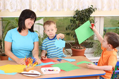 Preschoolers and manual skills. Teacher and two preschoolers making some decoration Royalty Free Stock Images