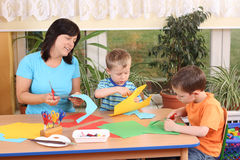 Preschoolers and manual skills. Teacher and two preschoolers making some decoration Royalty Free Stock Image