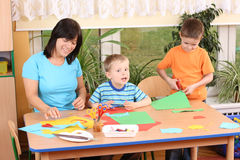 Preschoolers and manual skills. Teacher and two preschoolers making some decoration Royalty Free Stock Photo