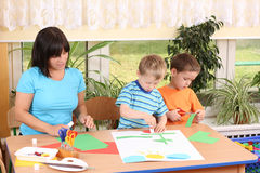Preschoolers and manual skills. Teacher and two preschoolers making some decoration Stock Photography