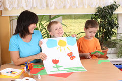 Preschoolers and manual skills. Teacher and two preschoolers making some decoration Stock Photos