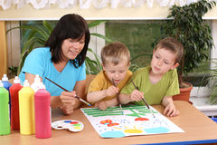 Preschoolers and painting. Teacher two preschoolers and colorful painting - education Royalty Free Stock Photo