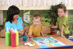 Preschoolers and painting. Teacher two preschoolers and colorful painting - education Stock Images