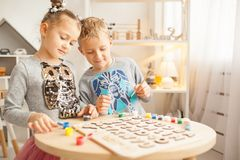 Preschoolers play and learn English letters using wooden alphabet. Preschooler girl and boy play and learn English letters using wooden alphabet stock image