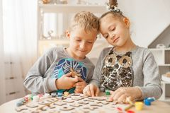 Preschoolers play and learn English letters using wooden alphabet. Preschooler girl and boy play and learn English letters using wooden alphabet royalty free stock image