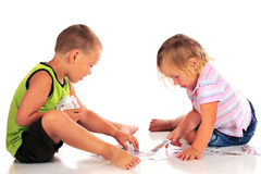 Preschoolers Playing Cards. Two barefoot  preschoolers playing with a deck of cards.  Isolated on white Royalty Free Stock Image