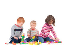 Preschoolers playing with wooden blocks. Three kids playing with wooden blocks. Isolated on white, with shadows Royalty Free Stock Photo