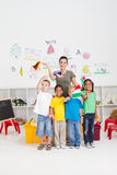 Preschoolers waving flags. A class of happy preschoolers and teacher waving different countries flags in classroom stock photography