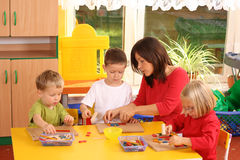 Preschoolers and wooden blocks. Teacher and three preschoolers playing with wooden blocks Stock Photos
