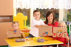Preschoolers and wooden blocks. Teacher and three preschoolers playing with wooden blocks Stock Images