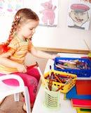 Prescooler del niño con el lápiz en sitio del juego. Fotografía de archivo
