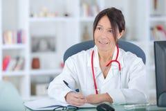 Prescrição fêmea da escrita do doutor para o paciente Foto de Stock