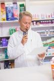Prescrição superior séria da leitura do farmacêutico Fotografia de Stock Royalty Free