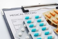 Prescribed medication. Medical record and pile of medicines. Many capsule medicines and tablets Royalty Free Stock Photo