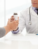 Prescribed medicines. Doctor giving a bottle of pills to the pat. Ient Royalty Free Stock Photography