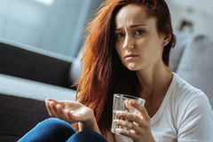 Sad ill woman preparing to take her medicine royalty free stock image