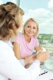 Prescribing vitamins. Portrait of confident practitioner prescribing vitamins to patient in hospital Royalty Free Stock Images