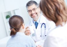 Prescribing vitamins. Confident practitioner speaking to patients about new vitamins in hospital Stock Image