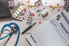Prescripción, estetoscopio y diversas píldoras coloridas, tabletas, cápsula en el fondo de madera blanco, visión superior Fotos de archivo libres de regalías