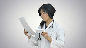 Prescripción femenina asiática de la lectura del doctor y mirada de la caja de medicina en el fondo blanco almacen de metraje de vídeo