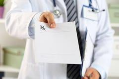 男性医学医生手举行剪贴板垫和给prescripti 免版税库存图片