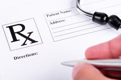 Prescription. Medical prescription with a stethoscope on top of it and a doctor about to write on it royalty free stock image