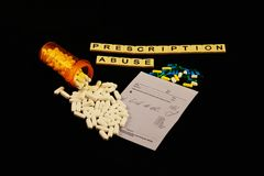 Prescription abuse is spelled out with tiles, spilled prescription pills on a prescription pad on a black background. Prescription abuse is spelled out in tiles Stock Images
