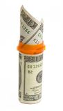 Prescription bottle with $20 bills isolated. A prescription bottle wrapped in a $20 bill with two $20 bills sticking out of it isolated against a white Royalty Free Stock Photo