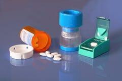 Prescription bottle, pills, pill crusher, splitter. An open bottle of prescription tablets and a pill crusher and a pill splitter are on a shiny blue background Stock Photos
