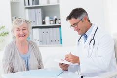 Prescription d'écriture de docteur tandis que sourire patient femelle images libres de droits