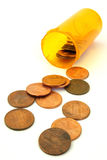 Prescription drug costs. A prescription drug bottle full of American pennies. Some of the pennies have spilled out. All are on a white background Royalty Free Stock Images