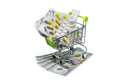 Prescription drugs on money representing rising health care costs. Isolated on white. medications in the cart. buying medicines stock photo