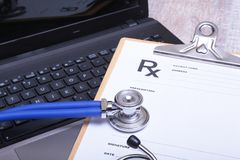 Prescription form with laptop computer and medical stethoscope Stock Photos