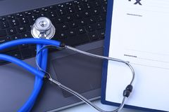 Prescription form with laptop computer and medical stethoscope Stock Image