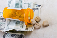 Heathcare costs. Prescription jar spilled on the counter with american bills Stock Image