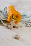 Heathcare costs. Prescription jar spilled on the counter with american bills Stock Photo
