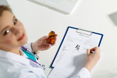 Prescription list. Beautiful young doctor sitting in front of working table , holding container with pills and writing prescription. Medical concept. Handsome Stock Photo