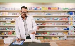 Prescription masculine d'écriture de pharmacien sur le lieu de travail photos stock