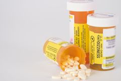 Prescription Medication Pill Bottles 10. Group of three prescription medication pill bottles with one open and small pills spilling out Stock Image