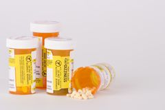 Prescription Medication Pill Bottles 3. Group of four prescription medication pill bottles with one open and small pills spilling out Stock Photo