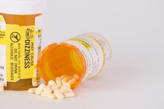 Prescription Medication Pill Bottles 5. Two prescription medication pill bottles with one open and small pills spilling out stock photos
