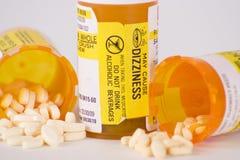 Prescription Medication Pill Bottles 6. Three prescription medication pill bottles with two open and small pills spilling out stock image