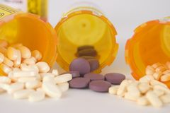 Prescription Medication Pill Bottles 8. Close up of three prescription medication pill bottles with all open and small pills spilling out Stock Photos