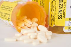 Prescription Medication Pill Bottles 9. Close up of two prescription medication pill bottles with one open and small pills spilling out Royalty Free Stock Photos
