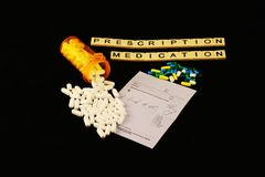 Prescription Medication spelled out with tiles, spilled prescription pills on a prescription pad on a black background. Prescription medication is spelled out in Royalty Free Stock Image