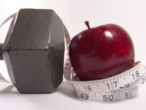 Prescriptions For Health. High resolution digital photo of an apple and a measuring tape symbolize healthy diet and body weight control. Dumbbell represents stock photos