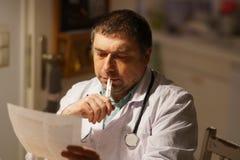 Prescrizione di scrittura di medico al suo scrittorio immagini stock libere da diritti