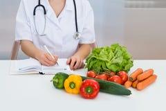 Prescrizione femminile di scrittura del dietista Immagini Stock