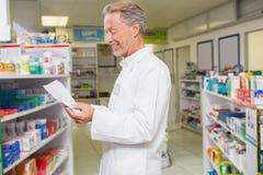 Prescrizione senior della lettura del farmacista Fotografie Stock