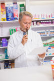 Prescrizione senior seria della lettura del farmacista Fotografia Stock Libera da Diritti